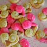 French Palmier Cookies shaped in hearts with white chocolate colored pink on one side side of the heart cookie, also with pink sprinkles