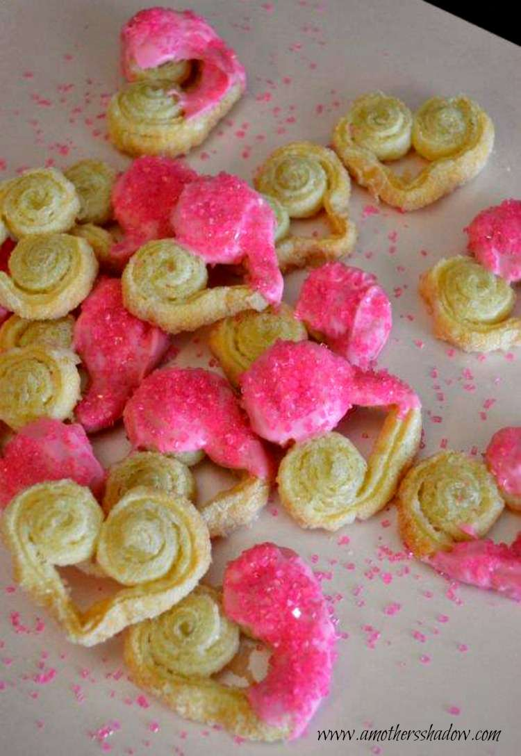 Easy Sweetheart French Palmier Cookies shaped in hearts with white chocolate colored pink on one side side of the heart cookie, also with pink sprinkles