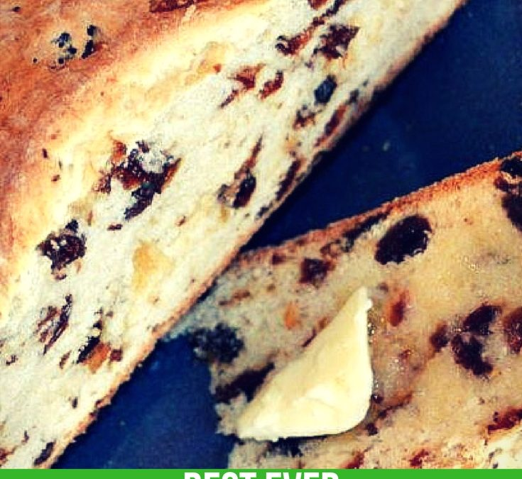 A delicious round loaf of the best traditional Irish Soda Bread with raisins is sitting on a plate. A couple of slices are sitting on the side of the plate with melted butter on them. The bread is moist, great flavor and makes scrumptious toast the next day.