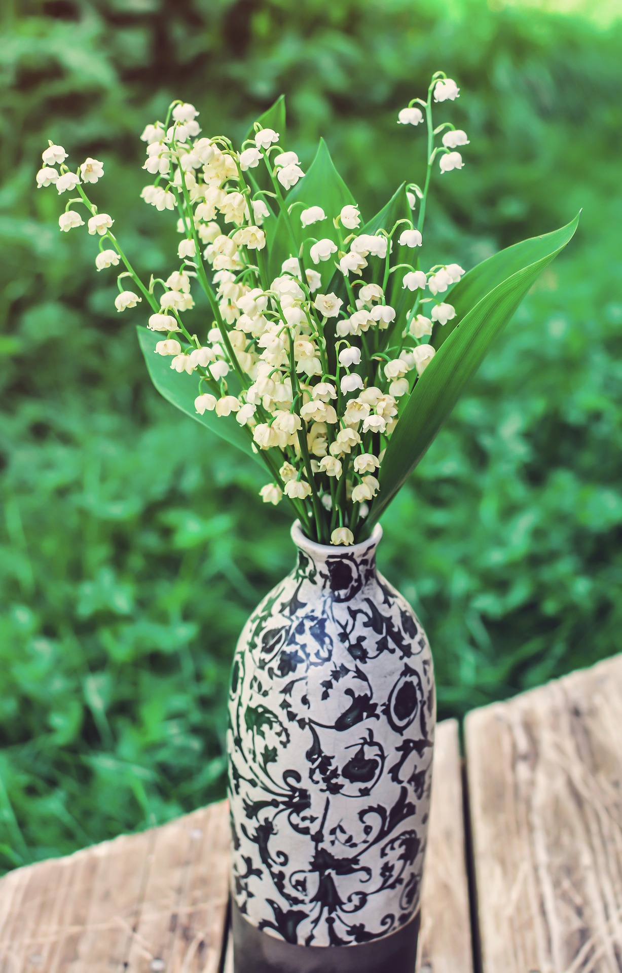A small decorated vase with a narrow opening so it doesn't require a lot of flowers. The flowers shown are Lilies of the field, but baby's breath, or mini carnations, or any inexpensive flower in a small vase, or a narrow opening vase would be wonderful