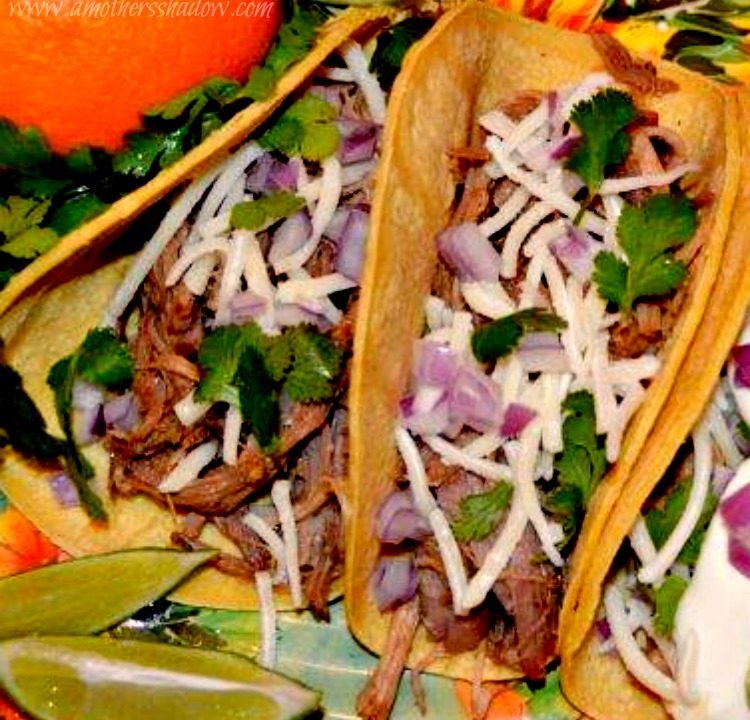 Two Cuban Street Tacos on a plate with an orange and 2 lime wedges. These tacos have orange and lime zest infused as the pork cooks along with Cuban inspired spices. The meat is in a tortilla, then shredded monterey jack cheese, diced red onion and cilantro.