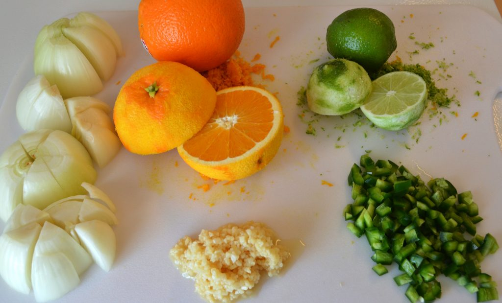 Cutting board with quartered onions, oranges zested and halved, limes zested and halved, chopped jalapeno and minced garlic