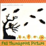 Kids thumbprint made into a pumpkin in a Halloween picture