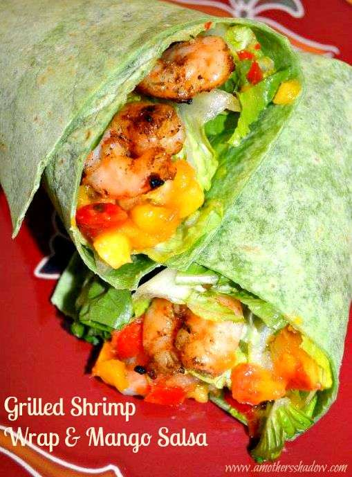 A tortilla with crisp romaine lettuce, bbq seasoned shrimp, mango salsa wrapped up