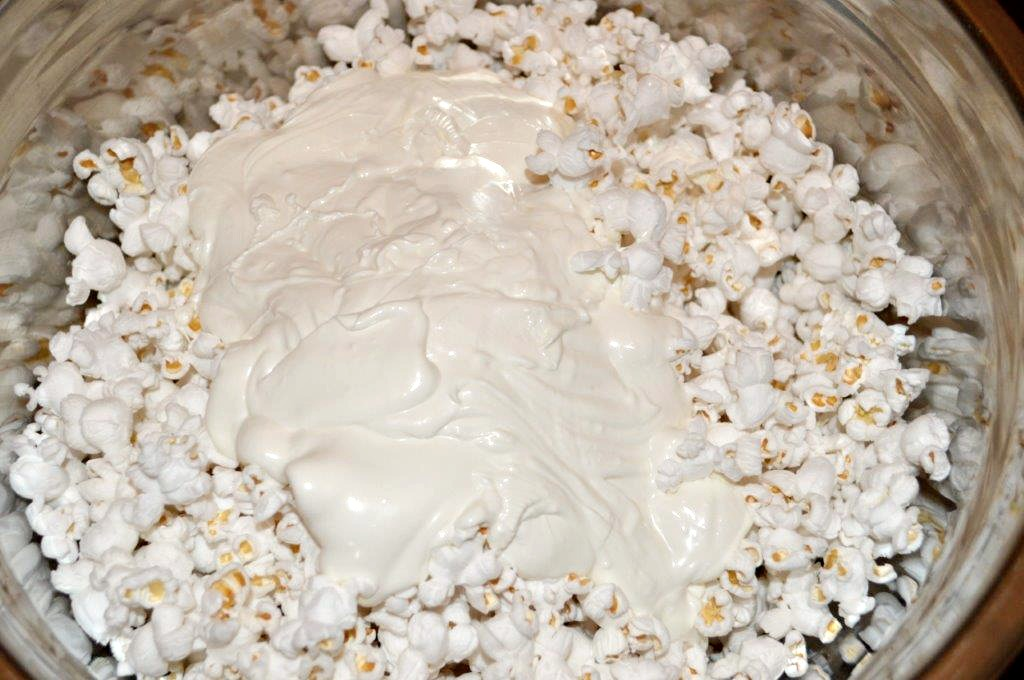A bowl of crunchy white popcorn covered in white chocolate. Mixed in are red and pink M&M candies for a Valentine Candy Snack Mix