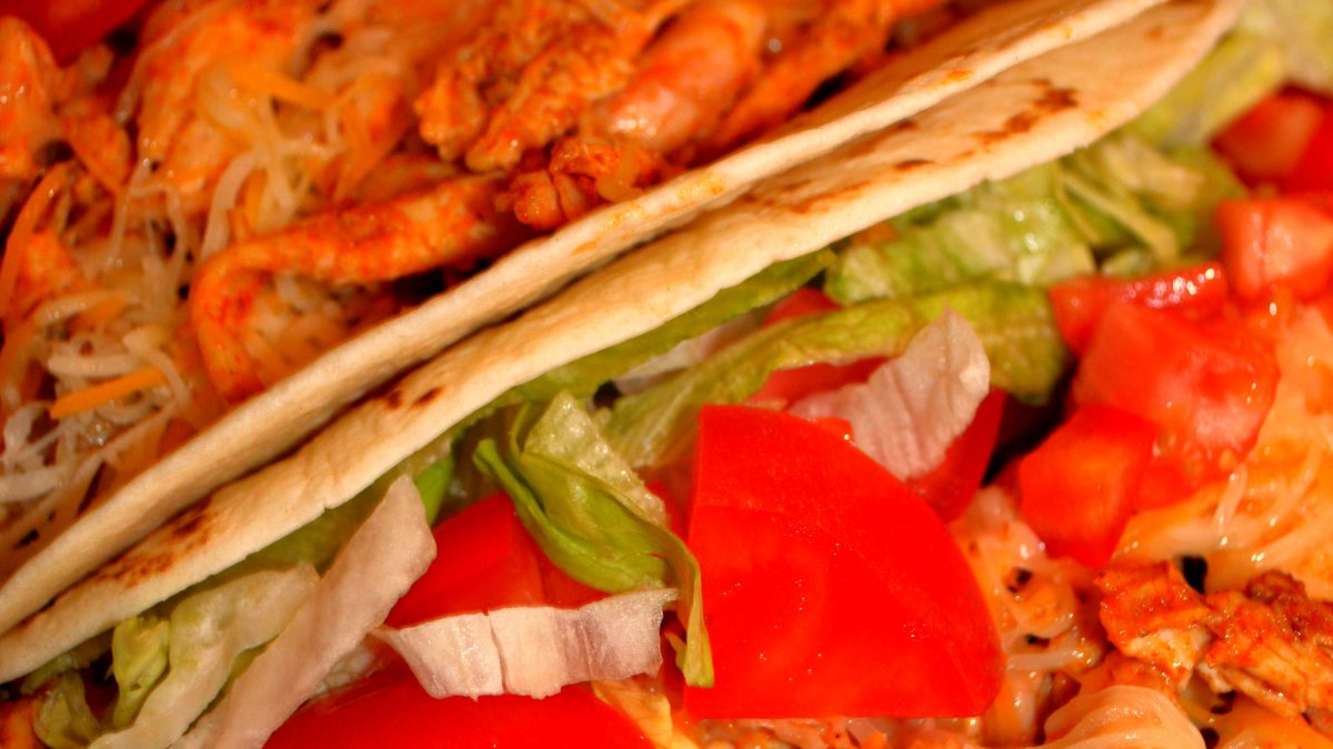Two chicken tacos in hard shells with shredded rotisserie chicken. Chopped tomatoes, lettuce are on top of the tacos for a delicious meal that's quick, easy and delicious for a busy weeknight or lazy weekend meal.