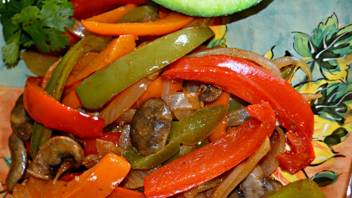 A beautiful plate of sauted peppers in several colors along with other vegetables all combined with the perfect spices to make this vegetarian fajita dish perfect for any meal.
